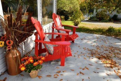 Muskoka chairs on a patio with fall decor.