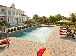 backyard landscape with a pool and patio set up