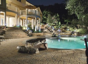 Beautiful backyard landscape with a pool at night.
