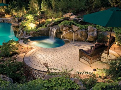 Beautiful and modern backyard landscaping design with a waterfall and inground pool.