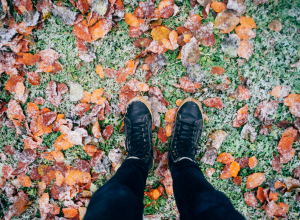 Person standing over grass and leaves with a layer of frost.